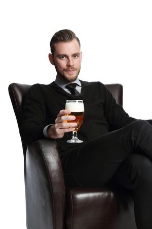 after to work: Un hombre de negocios joven y atractiva sentado despu�s del trabajo con una cerveza fr�a se relaja en un sof� vestido con una camisa jersey y corbata. Fondo blanco. Foto de archivo