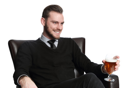 after work: A young and attractive businessman sitting down after work with a cold beer relaxing in a couch wearing a pullover shirt and tie. White background.
