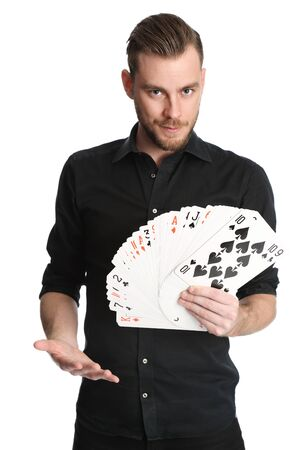 Young and attractive man wearing a black shirt with his sleeves rolled up holding a fan of big sized cards. White background.