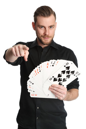 Young and attractive man wearing a black shirt with his sleeves rolled up holding a fan of big sized cards. White background. photo