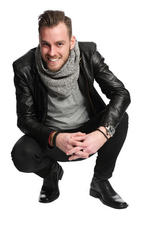Attractive man in a leather jacket and a grey shirt sitting down. White background.