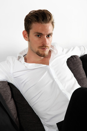 model male: Attractive young man in his 20s sitting down in a sofa, wearing a white shirt and black jeans. Feeling relaxed leaning back.