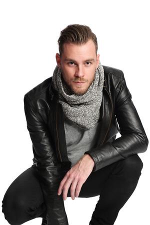 Attraktive Mann in eine Lederjacke und ein graues Hemd Sitzen. Weißen Hintergrund. Standard-Bild