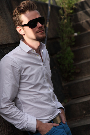 looking away from camera: A young and attractive man in his 20s standing outside on a set of steps, wearing a white shirt, blue jeans and sunglasses, looking away from camera.