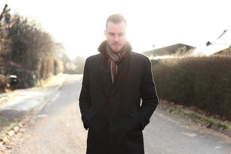 hombre solo: Apuesto hombre de unos 20 a�os, de pie al aire libre en un d�a de invierno con una chaqueta de color negro y bufanda mirando directamente a la c�mara. Pensativo con el sol directamente detr�s de �l.
