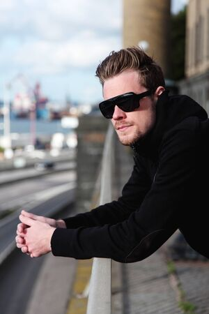 looking away from camera: A young and attractive man in his 20s standing outside, wearing a black hoodie and sunglasses, looking away from camera.