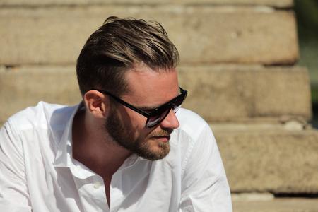 personas mirando: Retrato de un hombre guapo de unos 20 años, vestido con una camisa blanca con gafas de sol oscuras, sentado afuera en un conjunto de pasos en un día soleado de verano.