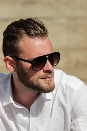 well laid: Portrait of a good looking man in his 20s, wearing a white shirt with dark sunglasses, sitting down outside on a set of steps on a sunny summer day. Stock Photo