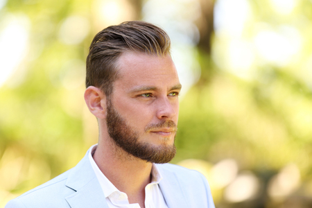 good looking model: Portrait of a man in his 20s wearing a light blue blazer and white shirt, standing against a green background on sunny summer day. Stock Photo