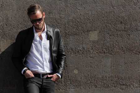 fashion sunglasses: A man in his 20s wearing a black leather jacket and white shirt, leaning back against a wall of stone on a sunny summer day,
