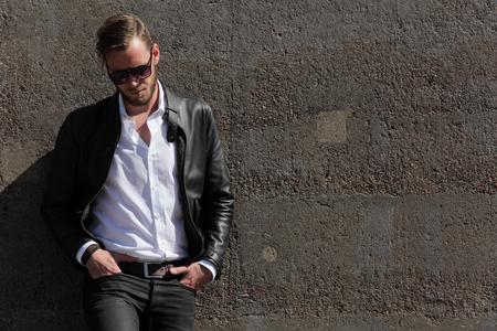 chaqueta: Un hombre de unos 20 años que llevaba una chaqueta de cuero negro y una camisa blanca, recostado contra una pared de piedra en un día soleado de verano,