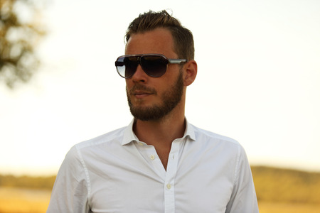 looking away from camera: A man wearing a white shirt and dark sunglasses, standing against a large yellow field looking away from camera. A great sunny summer day.