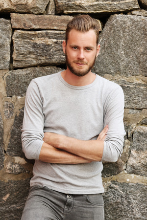 Attractive man wearing a grey sweater standing in front of a wall outside on a sunny summer day. Stock Photo