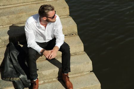 lifestyle outdoors: A handsome man in his 20s sitting down outside on a sunny summer day wearing a white shirt and black jeans with a leather jacket beside him. The river behind him.