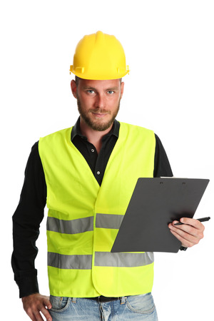 Attractive construction foreman in his 20s, wearing a yellow safety helmet with a yellow vest, holding a clipboard. White background.