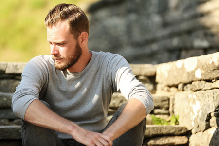 good looking model: Man in his 20s wearing a grey shirt and jeans, sitting down outside on a set of steps on a sunny summer day. Stock Photo