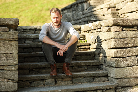 off path: Man in his 20s wearing a grey shirt and jeans, sitting down outside on a set of steps on a sunny summer day. Stock Photo