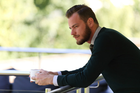 feeling positive: A pensive man wearing a pullover and holding a coffe mug, standing on a patio on a sunny summer day. Stock Photo
