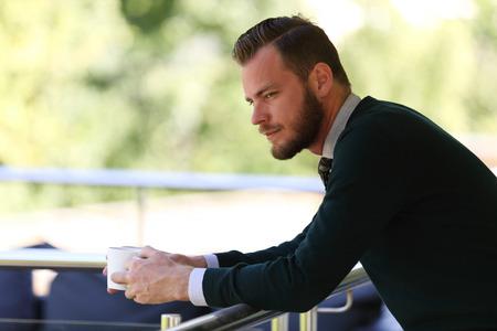 gente pensando: Un hombre pensativo que lleva un suéter y sosteniendo una taza de café, de pie en un patio en un día soleado de verano.