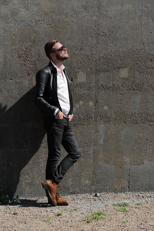 An attractive man wearing a black leather jacket and sunglasses leaning against a stone wall outside on a sunny summer day.