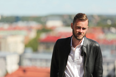 high up: A man in his 20s standing leaning back outdoors on a sunny summer day, wearing a black leather jacket and white shirt.