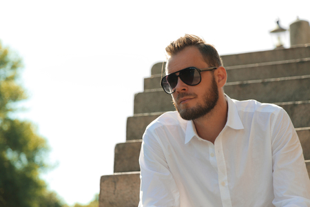 flare up: Attractive man wearing a white shirt and black jeans sitting down outside on steps, with dark sunglasses on a sunny summer day. Stock Photo