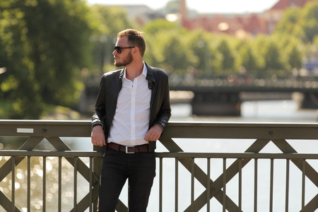 laid back: Attractive and laid back man leaning on a bridge with water behind on a sunny summer day. Wearing a leather jacket and white shirt. Stock Photo