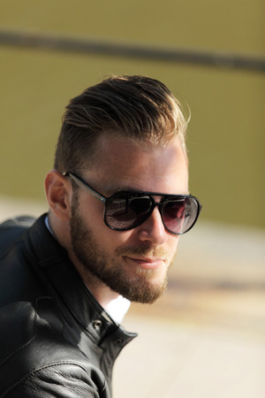 well laid: Portrait of a man wearing sunglasses and a black leather jacket, sitting down outside on a sunny summer day.
