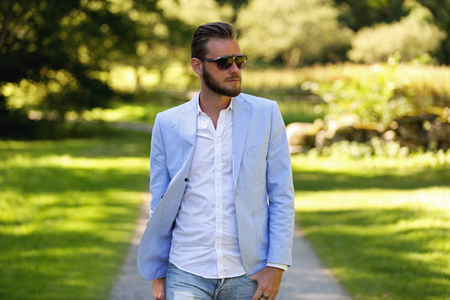 lonely person: Man wearing a blue blazer and sunglasses walking on a path on a sunny summer day.
