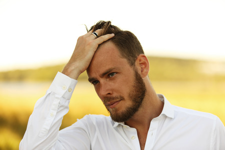 sweden resting: An attractive man in his 20s wearing a white shirt standing outside on a sunny summer day, with a big yellow field behind him.