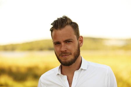 hombre solitario: Un atractivo hombre de unos 20 a�os que llevaba una camisa blanca de pie fuera en un d�a soleado de verano, con un campo amarillo grande detr�s de �l. Foto de archivo