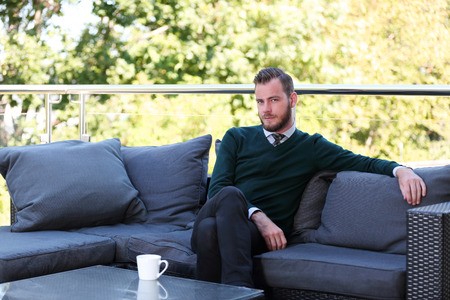 laid back: A handsome man in a shirt, tie and sweater sitting down outside on a summer day holding a mug. Relaxed and laid back.