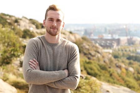 Trendy goed uitziende man die hoog op een berg met een prachtig uitzicht over de stad achter hem op een zonnige dag.