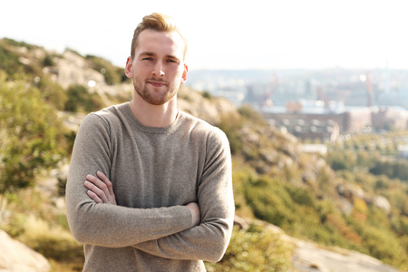 high up: Trendy good looking man standing high up on a mountain with a great view of the city behind him on a sunny day.