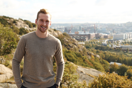 well laid: Trendy good looking man standing high up on a mountain with a great view of the city behind him on a sunny day.