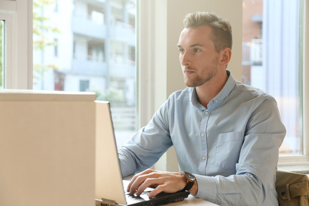 laid back: Young attractive adult wearing a blue shirt working on his laptop, studying. Mature and confident man. Stock Photo