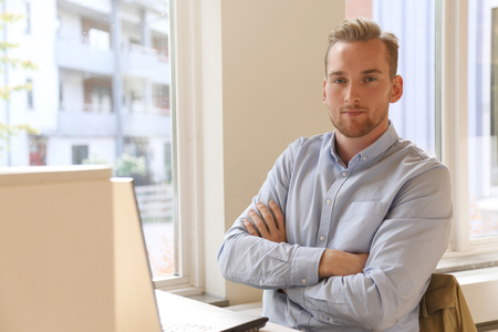 shirt: Young attractive adult wearing a blue shirt working on his laptop, studying. Mature and confident man. Stock Photo