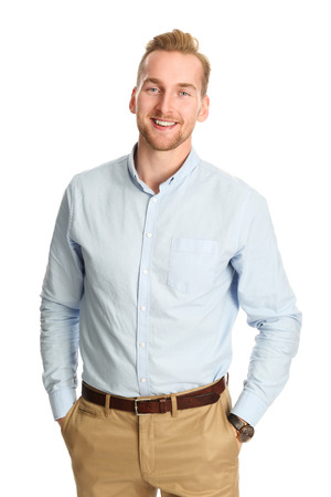 men shirt: An attractive young man wearing a blue shirt with khaki pants, standing smiling towards camera against a white background.