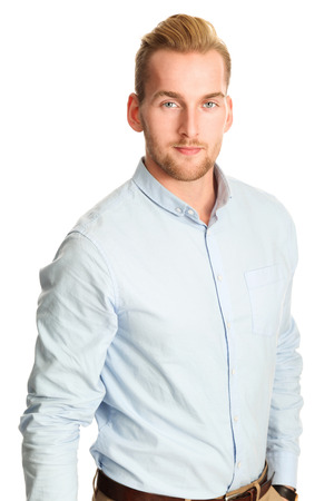 khaki pants: An attractive young man wearing a blue shirt with khaki pants, standing smiling towards camera against a white background.