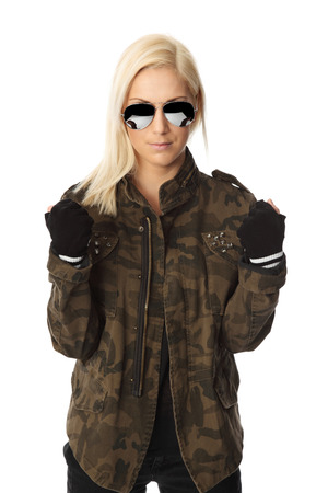 fingerless gloves: An attractive woman standing against a white background wearing a military jacket with big sunglasses. Macho looking.