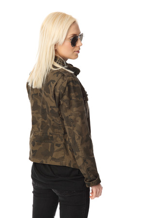 attractive macho: An attractive woman standing against a white background wearing a military jacket with big sunglasses. Macho looking.
