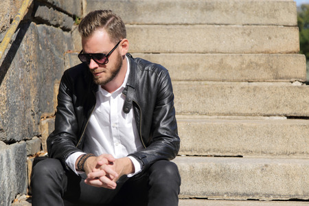 well laid: A handsome man in his 20s sitting down outside on a sunny summer day wearing a white shirt and black jeans with a leather jacket. The river behind him. Stock Photo