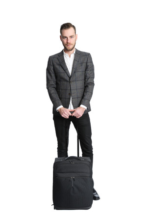 casual business: Attractive businessman on a travel wearing a blazer and white shirt. Holding a bag. Stock Photo