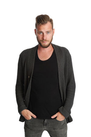 A man wearing a black shirt and grey sweater standing against a white background, smiling to camera. Stock Photo