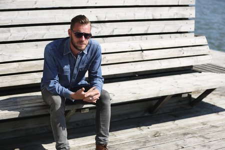 A lonely man sitting down outdoors wearing a jeans shirt and sunglasses, sitting close to the water in a harbor.