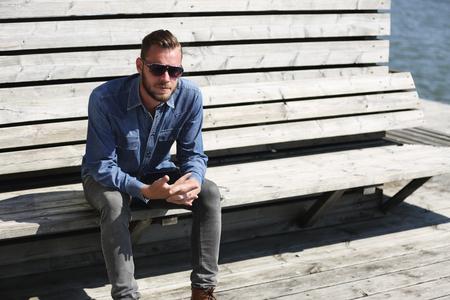 hombre solo: Un hombre solo sentarse al aire libre que lleva una camisa y gafas de sol pantalones vaqueros, sentado cerca del agua en un puerto.