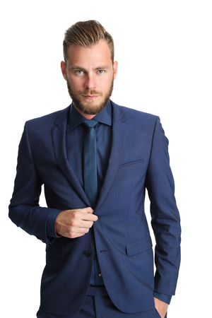 blue and white: A handsome businessman in his 20s standing looking at camera with a white background. Wearing a blue suit and blue tie. Stock Photo