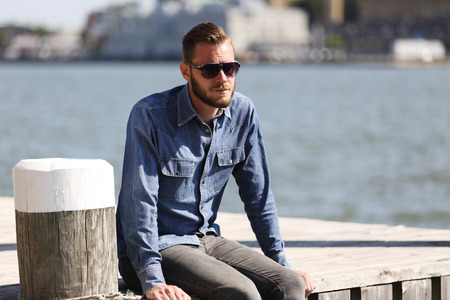 lonely man: A lonely man sitting down outdoors wearing a jeans shirt and sunglasses, sitting close to the water in a harbor.