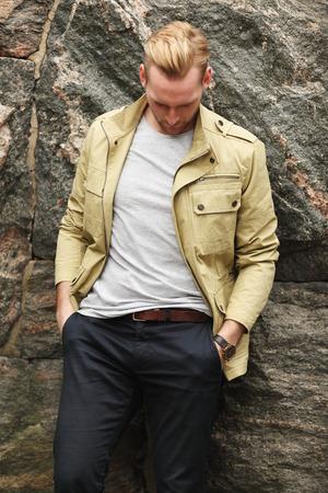 modelos hombres: Un hombre atractivo en un pantal�n chaqueta y amarillo oscuro, apoyado contra un muro de piedra al aire libre.