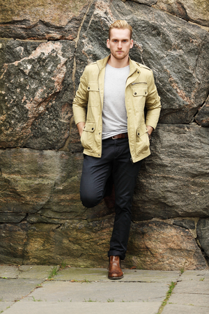 An attractive man in a yellow jacket and dark pants, leaning against a stonewall outdoors.